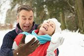 Senior Couple Having Snowball Fight In Snowy Woodland