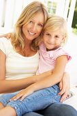 picture of mother daughter  - Portrait Of Mother And Daughter Relaxing On Sofa - JPG