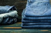 Bunch Of Jeans On Wooden Background, Fashionable Clothes poster