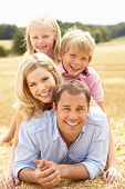stock photo of family fun  - Family Relaxing In Summer Harvested Field - JPG