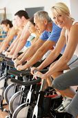 stock photo of senior class  - Senior Woman Cycling In Class In Gym - JPG