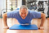 stock photo of senior class  - Senior Man Doing Press Ups In Gym - JPG