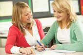 stock photo of student teacher  - Female Teenage Student Studying In Classroom With Teacher - JPG