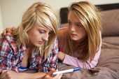 picture of teenage girl  - Two Teenage Girls Lying On Bed Looking At Pregnancy Testing Kit - JPG