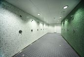big, light, empty public shower room, green tile on walls, gray floor