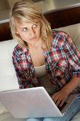 Schuldig aussehende Teenager-Mädchen mit Laptop zu Hause