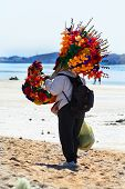 stock photo of peddlers  - Flower vendor carrying her paper mache flowers on the beach - JPG