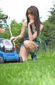 garden work, woman mowing grass with lawnmower