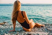 Beautiful Woman In Black Swimwear Relax On Sea With Warm Sunset Colors. poster