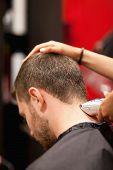 stock photo of clippers  - Portrait of a male young student having a haircut with a hair clippers - JPG