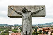 Jesus Is Hanging On A Stone Cross, A Cross With Jesus On A Background Of A City Landscape poster