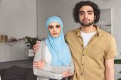 Affectionate Muslim Couple Looking At Camera At Home poster