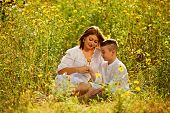 Mother And Son Having Fun. Son Giving Flowers To His Mother. Outdoor Shot. poster