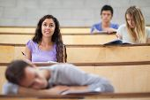 Students listening while their classmate is sleeping in an amphitheater