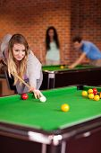 Portrait of a woman playing snooker in a student home