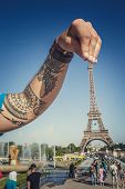 Tattooed Arm Abover Eifel Tower Over Blue Sky. poster
