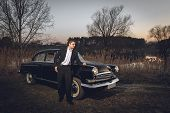 Young Handsome Groom Is Next Near To Black Retro Car Sunset Background. Wedding With Vintage Old Ret poster