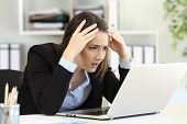 Worried Executive Complaining Receiving Bad News On Line In A Laptop At Office poster