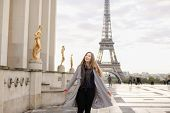 Beautiful Woman In Grey Coat Standing On Trocadero Square Near Gilded Statues And Eiffel Tower In Pa poster