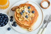 Tasty Pancakes With Bananas, Blueberries, Walnuts And Honey On White Plate. Closeup View. Stack Of H poster