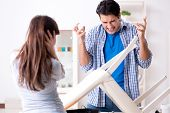 Wife helping husband to repair broken chair at home poster