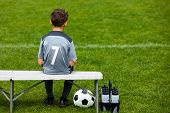 Little Footballer Sitting On A Wooden Bench And Watching Soccer Game. Young Substitute Player Waitin poster