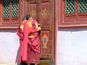 image of ulaanbaatar  - Two Buddhist monks wearing red opening a red wooden door at Gandantegchinlen Khiid in Ulaanbaatar - JPG