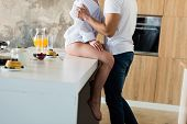 Cropped Shot Of Seductive Young Couple Hugging At Kitchen Table During Breakfast poster