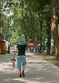 Dad Holds Scooter And His Son On The Neck Walking In A Green Summer Park. Walking A Dad With His Son poster