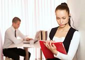 Attractive customer service operator talking on headset, male colleague sitting in the background.
