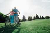 Senior Couple With Their Bicycles Standing And Hugging, Rear View. Active Rest Of The Elderly People poster