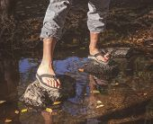 woman crossing a creek with flip flops on toned with a retro vintage instagram filter   poster