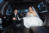 foto of limousine  - Bride and bridegroom in a luxury wedding limousine - JPG