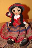 pic of chola  - andean child chola cholito doll dolls mother peru peruvian shapes traditional colors crafts craftsmanship culture folk fur objects travel swirl warmth weaving wool yarn hat face happy - JPG