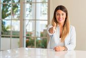 Young beautiful woman at home holds hands welcoming in handshake pose, expressing trust and success  poster