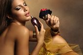 stock photo of perfume  - elegant sensual young woman holding perfume - JPG