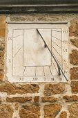Modern stone sun dial set in a stone wall with Roman numerals