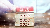 Businessman Builds Wooden Blocks 2020. The Concept Of The Beginning Of The New Year. New Goals. Next poster