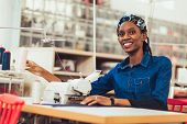 Young African Textile Worker Sewing On Production Line. Dressmaker Woman Working With Sewing Machine poster