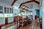 Large expensive chefs kitchen in luxury home with rough hewn wood and white cabinets. poster
