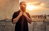 Tattooed And Bearded Guy In Sunglasses Adjusting Stylish Jacket And Looking Away While Standing Near poster
