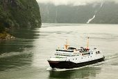 Fiord with white passenger liner near mountain with waterfalls