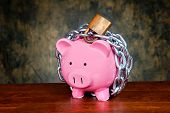 A pink piggybank chained up and locked. Image can be used for financial protection inferences or oth