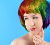image of ordinary woman  - A woman has rainbow colored hair against a blue background - JPG