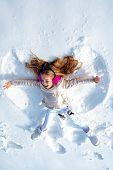 Smiling Child Lying On Snow With Copy Space. Funny Kid Making Snow Angel. Child Girl Playing And Mak poster