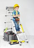 Little Boy Handyman With Helmet And Tool Belt On Stepladder