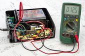 stock photo of transistor  - Testing old battery voltage with digital multimeter - JPG