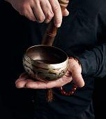 Man In A Black Shirt Rotates A Wooden Stick Around A Copper Tibetan Bowl. Ritual Of Meditation, Pray poster