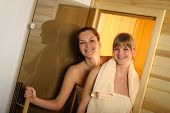 Happy women getting out of sauna at spa center