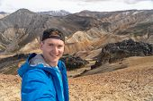 Hiker With Backpack Taking Selfie In The Landmannalaugar Valley. Iceland. Colorful Mountains On The  poster
